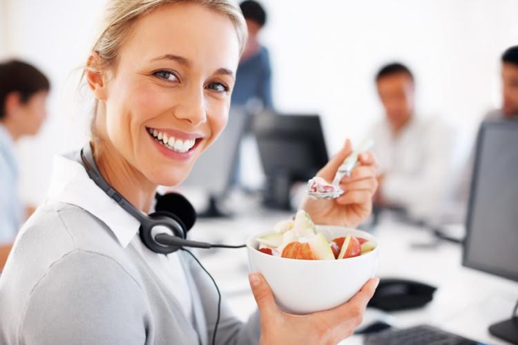 Closeup of female customer executive eating bowl of fruit salad with colleagues in background